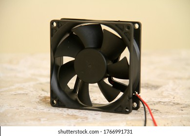 Small dc computer fan standing on surface closeup