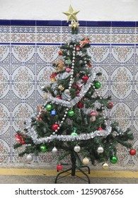 Small decorated artificial christmas tree on pavement against tiled wall in Andalusian village street