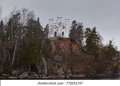 A small decorative castle with white towers on the background of the forest  on the mountain. Close-up of the fortification building.