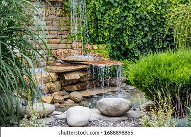 A small decorative waterfall in the garden. Landscape design