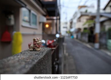 Small deity protects entrance to Japanese home on street