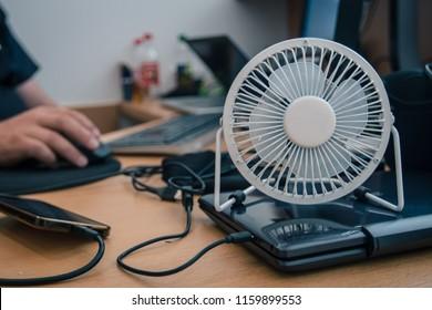 Ein kleiner USB-Fächer oder Ventilator für den Desktop, der den Bereich auf einem Schreibtisch mit Desktop-Computer abkühlt. Hände einer Person, die im Hintergrund arbeitet.