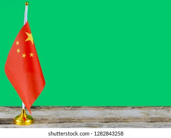 A small, desktop version of the flag of China on a wooden table with a green screen for your own background. Good for Chinese New Year, Spring Festival, lantern Festival, political, economic  concept