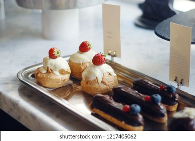 Small desserts in a vitrine of a cafe, mini cakes and eclairs