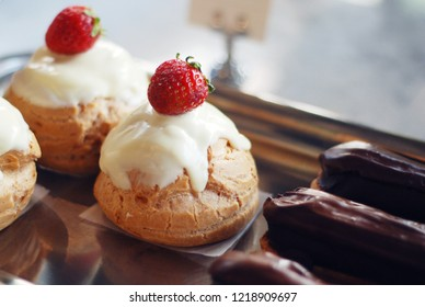 Small desserts in a vitrine of a cafe, mini cakes and eclairs closeup