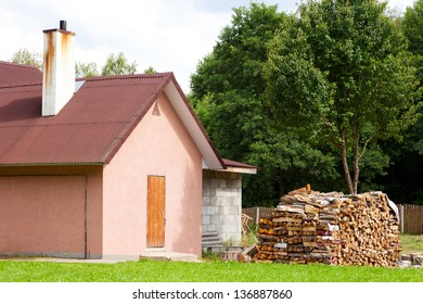 small detached house with firewood outside