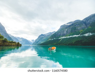 Small dinghy on blue lake in Norway. Beautiful Norwegian landscape, Lovatnet.