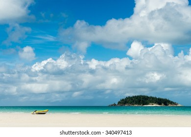 A small dingy sits on the white sand beach of Whitsunday Island, Australia.