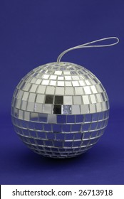 Small disco ball with hanger on a blue background.
