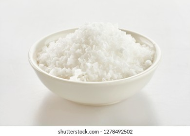 Small dish of clean white Flor de Sal, a culinary salt derived from the surface of seawater by evaporation over white