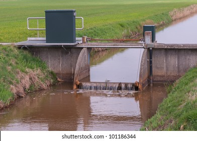 Small ditch with a weir between meadows in the Netherlands.