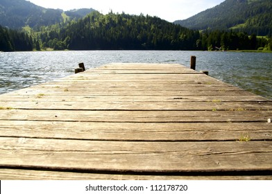 Kleiner Dock, der in einem See in den Alpen führt