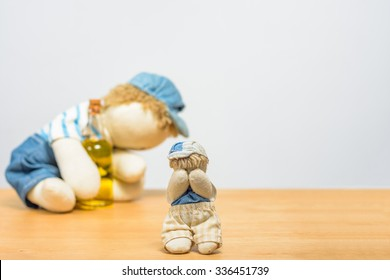 A small doll crying because of his drunk father