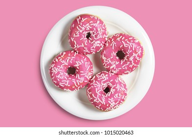 Small donuts with sprinkles in white plate on pink background, top view