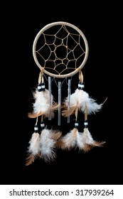 A small dream catcher with feathers, beads and chimes on a pure black background