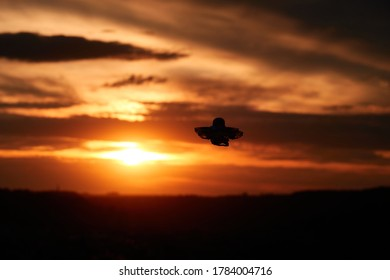 Small drone also multicopter as a silhouette. Orange evening sky with clouds, city in the background. Germany.