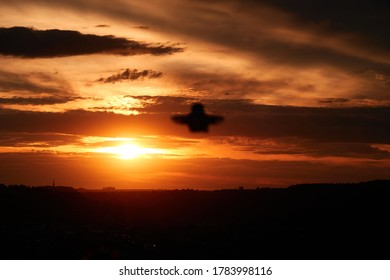 Small drone also multicopter as a silhouette out of focus. Orange evening sky with clouds, city in the background. Germany.
