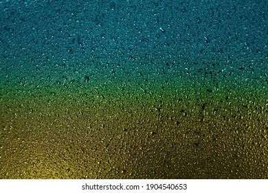 Small drops of water or condensate on the metal surface are yellow and blue. Abstract background for a screen saver or backdrop. Top view