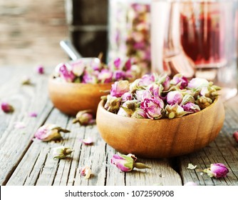 small dry buds of roses, tea, karkade, in wooden bowls on wood table, selective focus