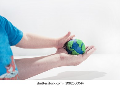 Small Earth model with human hands. Abstract composition of peace.
