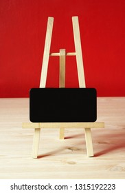 small easel. Background with empty easel on wooden table. Background with black phone on wooden table over red background.