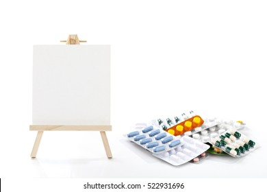 Small easel with white album sheet of paper and bunch of pills