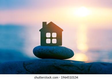 Petite maison éco en bois sur la plage de mer au coucher du soleil, voyage en famille et vacances d'été, spiritualité, concept de solitude
