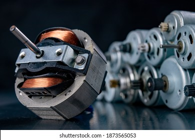 Small electric motors used in household appliances. Devices for driving various small devices. Dark background.