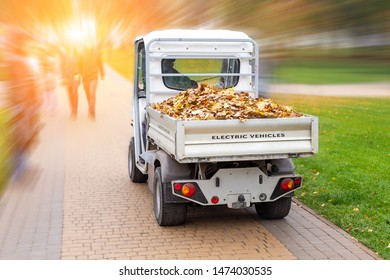 Small electric truck removing fallen leaves in body at autumn city park. Municipal urban services using ecology green vehicle lorry to clean streets from foliage