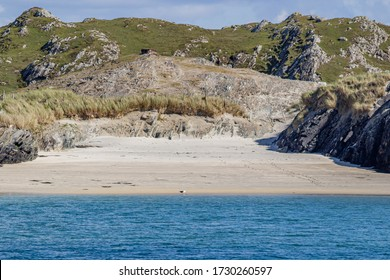 Small empty beach with calm blue water between rocky hills with green grass, sunny spring day on Inishbofin Island, County Galway, Ireland