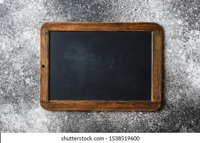 Small empty chalkboard on a grey textured background. Blank. Blackboard Background. Blackboard texture