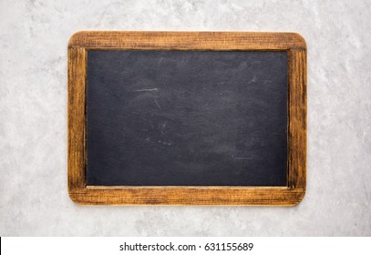 Small empty chalkboard on a light grey textured background. Blank. Blackboard Background. Blackboard texture