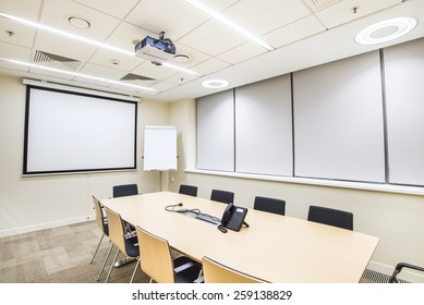 Small empty meeting room with TV projector and flipchart