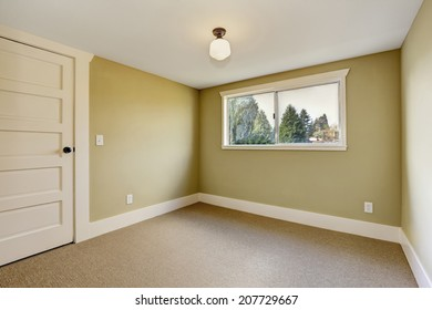 Small empty room with window and beige carpet floor
