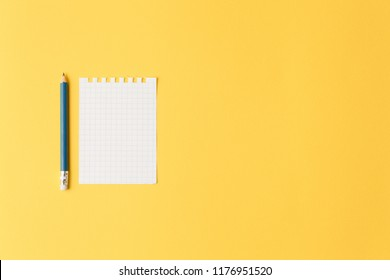 small empty sheet of paper on a yellow isolated background, top view and lots of free space. flat lay. sheet of tasks and office concept, a sticker for notes