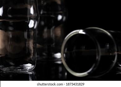 Small empty shotglasses on a dark background in dramatic lighting. Alcohol help problem dark