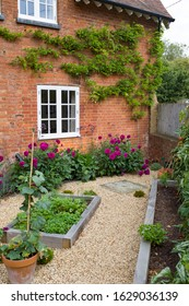 Small English courtyard garden in UK with oak sleeper raised beds, gravel, and a Victorian house