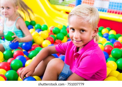 Small european boy in elementary school age sitting and playing with multicolored plastic balls