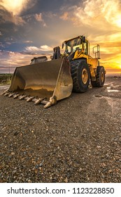 Small excavator in a beautiful sunset in the expansion works of the ring road in Segovia (Spain)