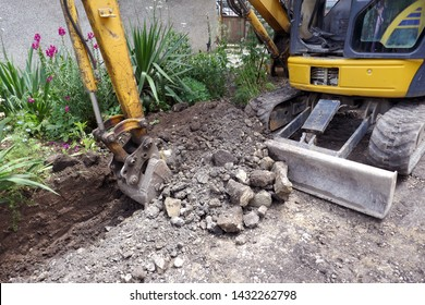 Small excavator is excavating soil at construction site, project in progress