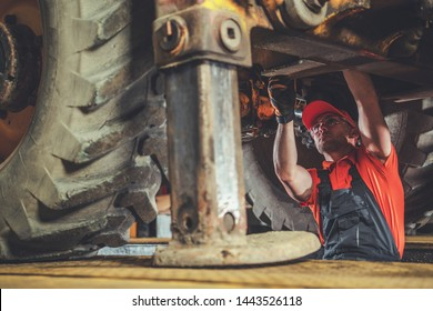 Small Excavator Repair and Maintenance. Caucasian Heavy Equipment Mechanic Trying to Find an Issue. Industrial Theme.