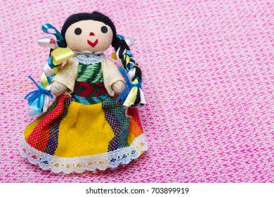 Small fabric doll girl in colorful dress of Mexico on pink background.