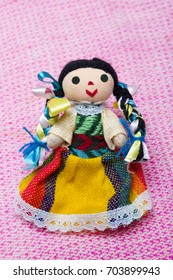 Small fabric mexican doll girl in colorful dress of Mexico on textile background.