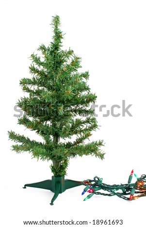 small fake green christmas tree waiting to be decorated on a white background with colorful christmas
