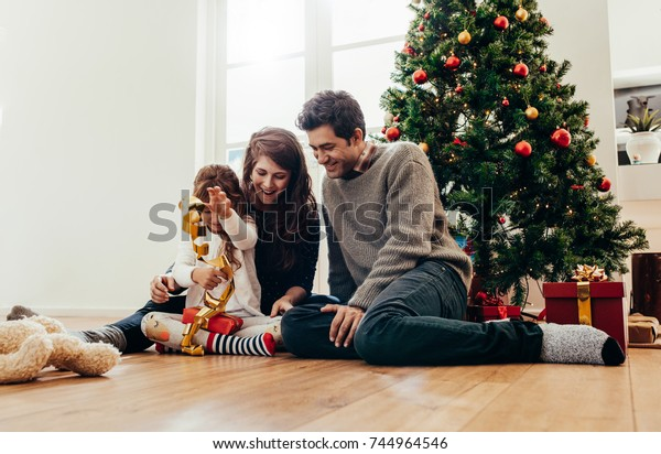 Small family having happy time together on Christmas. Young couple with child sitting beside Christmas tree opening gifts.
