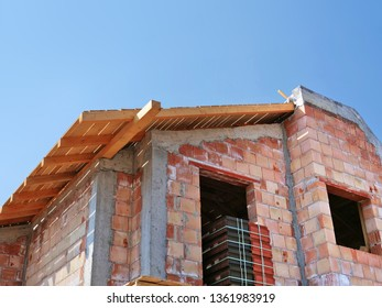 Small family house building in progress. Clay brick walls with wood decking for tile roofing.