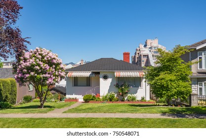 Small family house with flowers and trees on front yard. Modest residential house on sunny day in British Columbia