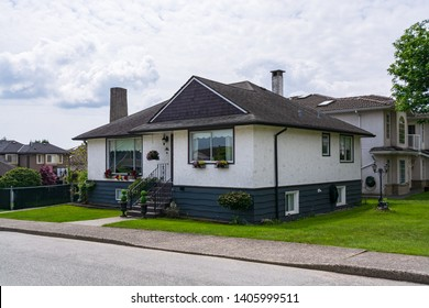 Small family house with green lawn in front.  Average residential house on cloudy day in British Columbia