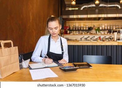 Small family restaurant owner doing finance calculating bills and expenses of small business – young woman counting profit of store at the end of day – waitress accounting at table
