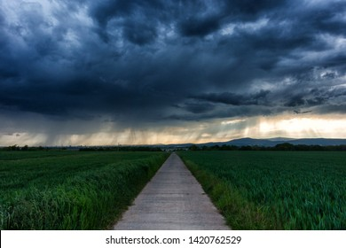 Small farm road in front of an approaching storm, Wetterau, Hesse, Germany